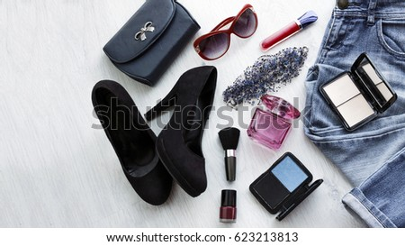 Close up trendy accessories for young woman. Overhead clutch, jeans and black shoes #623213813