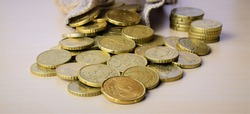 Close up , twenty cents euro coin, outline scattered with a small fabric bag in the background