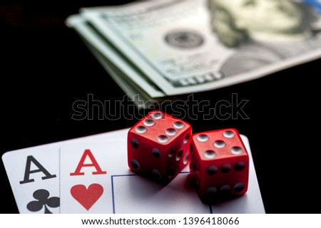 Close-up - Two aces, playing cards, red gaming dices and Stack of american dollars on black table. Casino, gambling game chance concept #1396418066