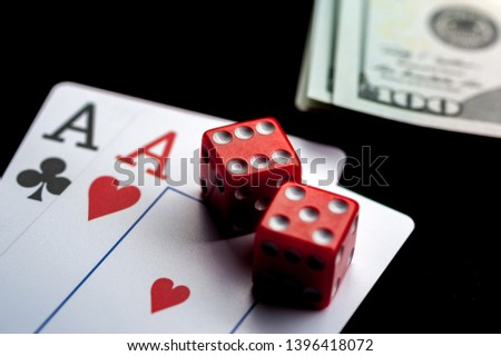Close-up - Two aces, playing cards, red gaming dices and Stack of american dollars on black table. Casino, gambling game chance concept #1396418072