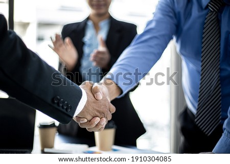 Close-up two business men holding hands, Two businessmen are agreeing on business together and shaking hands after a successful negotiation. Handshaking is a Western greeting or congratulation.