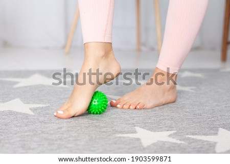 close-up two feet with a pedicure of a young woman, one foot stands on a green spiky massage ball on a carpet in a home interior. Stockfoto ©