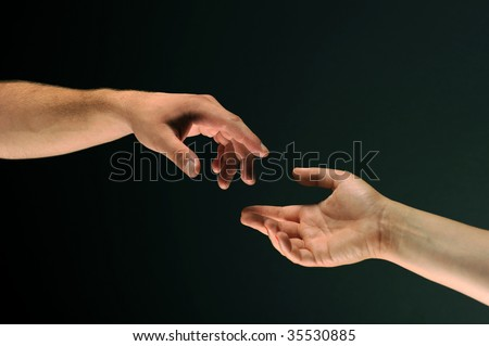 Close-up two hands reaching to each other