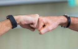 Close up two male hands making gesture of fists or knuckle bumping or hitting for greeting, congratulating successful business achievement, cooperating with unity power or fighting in competition