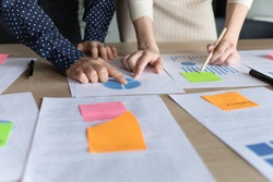 Close up two multiracial business women analyzing marketing research charts on paper document, developing economic growth strategy, managing working processes using memo colorful stickers in office.