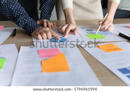 Close up two multiracial business women analyzing marketing research charts on paper document, developing economic growth strategy, managing working processes using memo colorful stickers in office. Foto stock ©