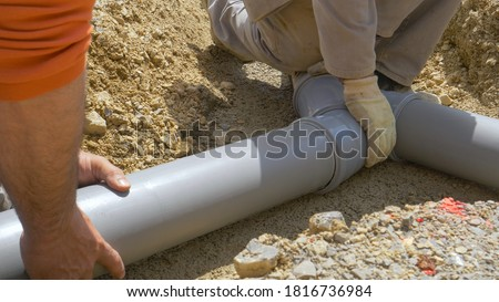 Photo of  CLOSE UP: Two plumbers assemble grey pvc sewage pipes during maintenance works. Unrecognizable contractors work together to create a wastewater drainage system for a nearby house under construction