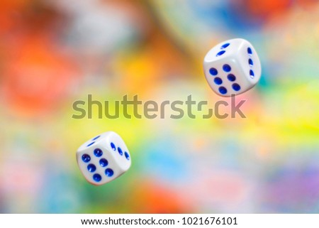 close up two Rolling dice on blurred colorful background. Board games, gaming moments in dynamics. concept of luck, winning, victory #1021676101