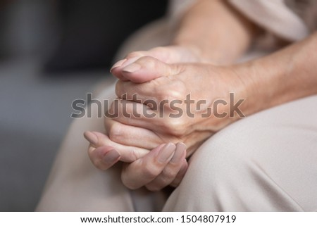 Close up unhappy lonely mature woman folded hands together, sitting on couch alone, upset desperate older female thinking about life, health or emotional problem, feeling sad, suffering from anxiety