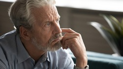 Close up unhappy pensive older man thinking about problems, lost in thoughts, looking into distance, sitting alone, sad upset mature male feeling lonely, nostalgia and melancholy