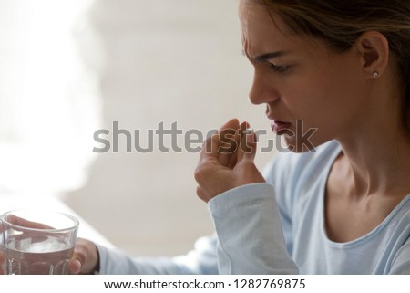 Close up unhealthy woman hold glass still water and painkiller pill, taking antidepressant or antibiotic medicine, sick female suffering from headache or insomnia, emergency treatment concept close up