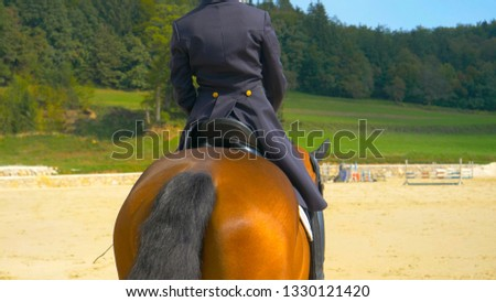 CLOSE UP: Unrecognizable girl in a blue frock riding a horse around the empty manege. Active woman horseback riding during an English dressage competition. Well dressed girl riding a muscular stallion