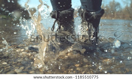 CLOSE UP: Unrecognizable girl in fluffy black boots stomping her feet in the glassy river. Crystal clear lake water splashes around the unknown playful woman's feet as she jumps around autumn nature.