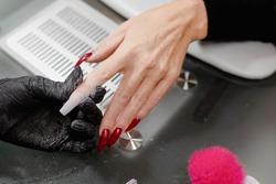 Close up unrecognizable woman hands. Manicurist applying gel on client's fingernails with stiletto shape. Nail reconstruction, polish, manicure concept.