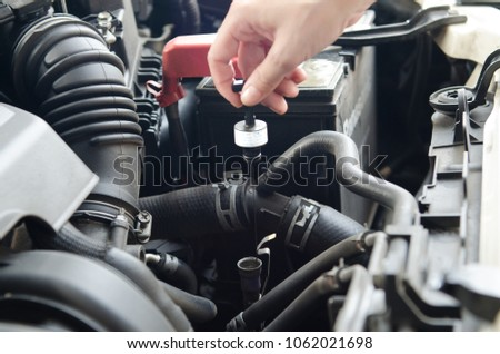 Close up unrecognized hand of mechanic female doing car services and maintenance. check up engine oil