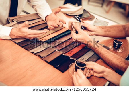 Close Up. Upholstery Color Choosing In The Store. Furniture Seller. Customer And A Buyer. Making A Purchases. Bright Office. Cup Of Coffee. Good Mood. Shopping Activity. Manager In A Suit. #1258863724