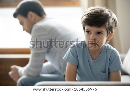 Close up upset little boy and father ignoring each other, not talking after quarrel, unhappy preschool son and dad sitting on couch separately, parent and child, family generations conflict Stok fotoğraf ©