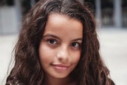 Close up urban lifestyle portrait of a confident, gorgeous mixed race child face, head shot of multiethnic tween preteen teen girl with beautiful curly hair, smiling at camera, youth day