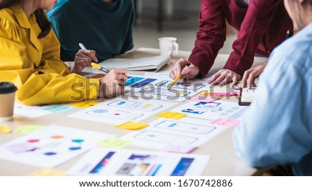 Close up ux developer and ui designer brainstorming about mobile app interface wireframe design on table with customer breif and color code at modern office.Creative digital development agency