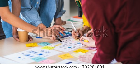 Close up ux developer and ui designer brainstorming about mobile app interface wireframe design on table with customer brief and color code at modern office.Creative digital development agency.panning