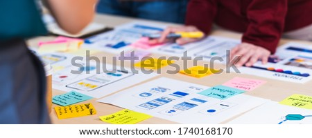 Close up ux developer and ui designer brainstorming about mobile app interface wireframe design on table with customer brief and color code at modern office.Creative digital development agency.panning Stockfoto ©