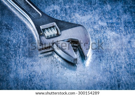 Close up version of stainless adjustable spanner on scratched metallic background construction concept.