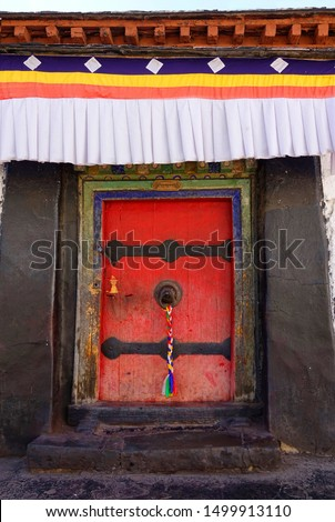CLOSE UP, VERTICAL: Colorful banner hangs above a door with a braid of prayer flags hanging from a metal ring. Front door of a building in Sakya monastery with a knocker with a multicolored braid. #1499913110