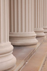 Close up vertical view of beige stone Greek columns, base and stairs texture backgrounds