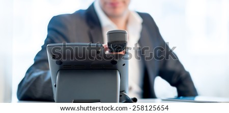 Close up view across the desk of the hands of a businessman making a  phone call as he sits at his desk in a communications concept.