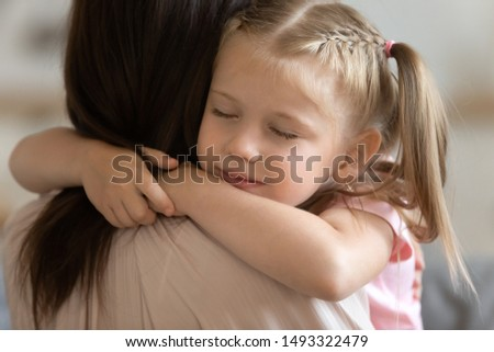 Close up view adorable daughter face closed eyes embraces loving mother rear back view, concept of deep connection and love, adopted child and new mom showing sincere gratitude, say sorry and apology