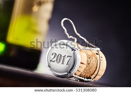 Close up view at angle of the year 2017 on end of cork and metal cap. Wine bottle of focus in background.