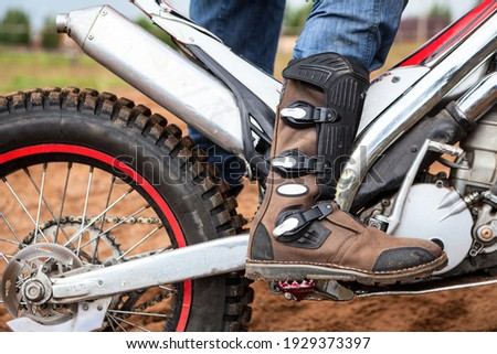Close-up view at rider's motocross boot standing on peg of dirt motorcycle. Safety apparel for riding Foto stock ©