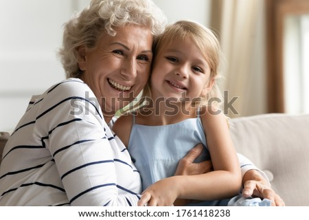 Close up view blond little granddaughter spend time pose looking at camera photo shoot with elderly funny cheerful carefree grandmother. Life value, next and older generation strong connection concept