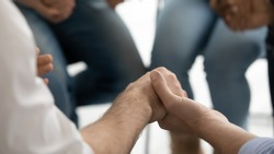 Close up view christian people group holding hands and praying together sitting in circle indoor during devotional meeting. Girls and guys overcome bad habit at therapy rehab session reunion concept