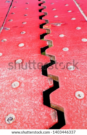 Close up view from above of an red iron dilatation joint placed on a opening bridge road - Zigzag line from steel #1403446337
