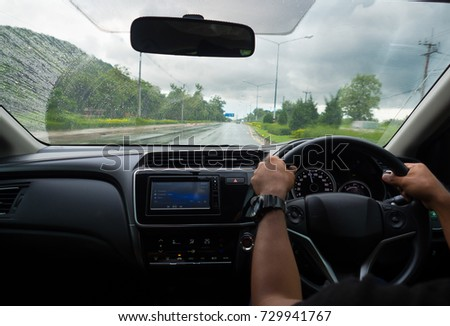 Close-up view from the car driving. Hands of a driver on steering wheel of a car and asphalt road. Journey on the road with speed in a rainy day