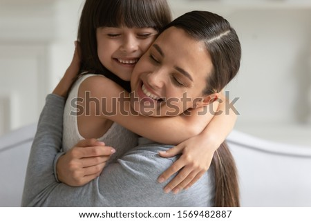 Close up view happy gorgeous young mother strong cuddle little candid daughter, concept of adopted child and new mommy, connection and devotion of mom and small kid, sincere feelings love and caress