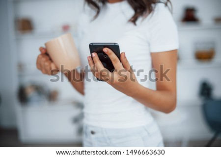 Close up view. Holds cup of drink in hand. Woman in white clothes with her smartphone resting in living room.
