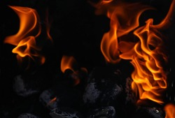 Close up view inside the bbq grill on burning open fire with red flame, hot  charcoal briquettes and embers. Abstract background and natural texture