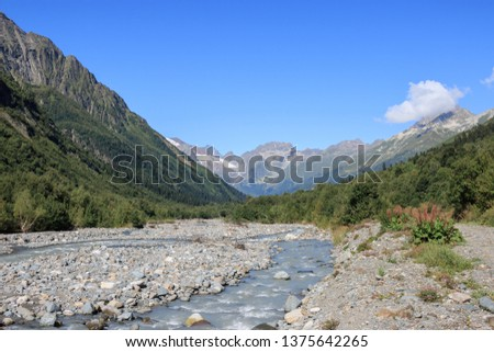 Close up view mountains and river scenes in national park Dombay, Caucasus, Russia, Europe. Summer landscape, sunshine weather, dramatic blue sky and sunny day