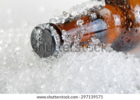 Close up view of a beer bottle neck covered with ice and condensation. Layout in horizontal format. Focus on bottle cap with shallow depth of field.