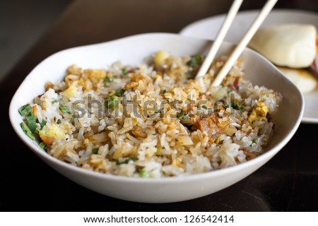 Close up view of a bowl of bacon fried rice with a pork man tau bun.