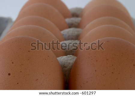 Close-up view of a carton of brown eggs, viewed from the end.