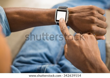 Close up view of a casual man using smart watch in living room