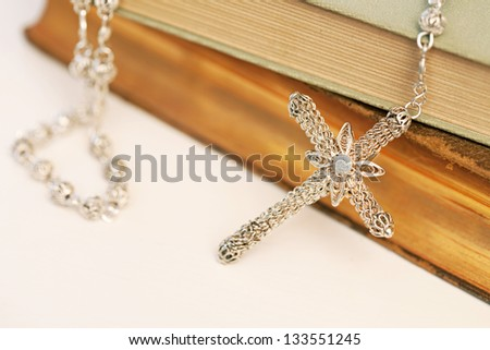 Close up view of a catholic religious books with a silver decorated praying rosary resting on it.