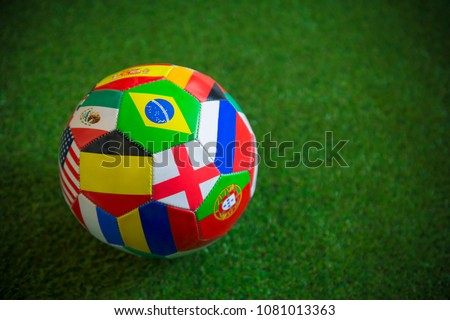 Close up view of a classic world flag football on lush green grass background. Unique, home-made football prop.