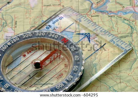 Close-up view of a compass sitting on a topo map.