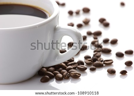 close-up view of a cup of coffee and coffee beans on white background