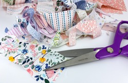Close up view of a dressmaking scissors with a pile of scraps of printed patterned fabric