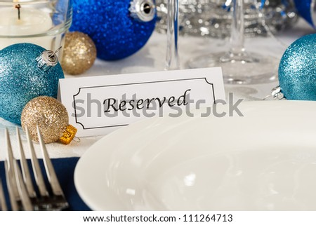 Close up view of a holiday table setting with an empty plate providing copy space is decorated with blue and gold ornaments and a placard showing a reserved place